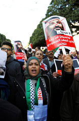 Woman holds a banner during a protest opposing the visit of Saudi Arabia's Crown Prince Mohammed bin Salman in Tunis