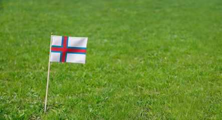 Faroe Islands flag. Photo of Faroe Islands flag on a green grass lawn background. Close up of national flag waving outdoors.