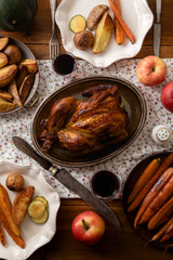 Traditional festive dinner with roasted chicken, apples and verious garnishing on wooden table, covered with patterned tablecloth