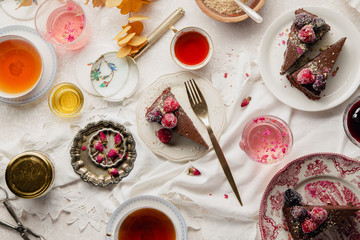 Overhead image of tea party with chocolate cheesecake slices on various plates. Traditional style, vintage tablecloth and cutlery.