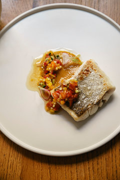 Hake fish served with vegetables on a white plate