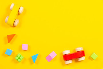 Baby kids toys background. Wooden car, colorful bricks and cubes on yellow background