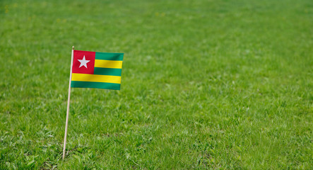 Togo flag. Photo of Togo flag on a green grass lawn background. Close up of national flag waving outdoors.