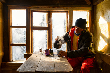 Traveler is drinking coffee and dreaming in a old mountain hut