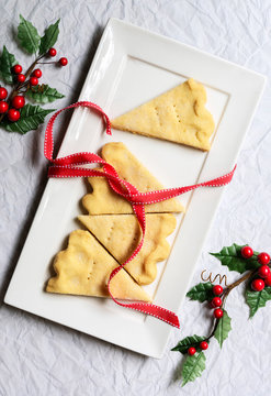 Pieces of shortbread on a plate decorated with red ribbon and holly.