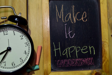 Make It Happen on phrase colorful handwritten on chalkboard and alarm clock with motivation, inspiration and education concepts. Table background