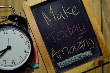 Make Today Amazing on phrase colorful handwritten on chalkboard and alarm clock with motivation, inspiration and education concepts. Table background