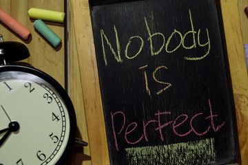 Nobody is Perfect on phrase colorful handwritten on chalkboard and alarm clock with motivation, inspiration and education concepts. Table background