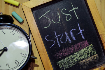 Just Start on phrase colorful handwritten on chalkboard and alarm clock with motivation, inspiration and education concepts. Table background