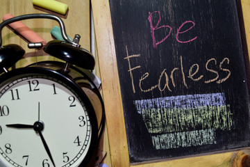 Be Fearless on phrase colorful handwritten on chalkboard and alarm clock with motivation, inspiration and education concepts. Table background