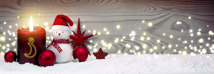 Christmas background with third Advent candle and Snowman with red decoration.