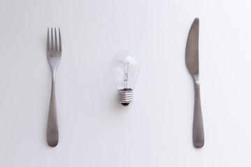 Light bulb, fork and knife on the white table. Electricity consumption, intellectual property concept. Top view, flat lay, copy space