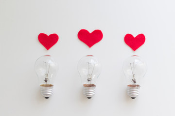 Three lamp bulbs with red felt hearts on the white background. Top view, flat lay, copy space