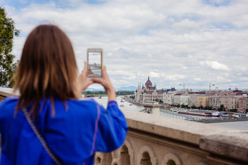Woman taking a picture with her smartphone at Budapest Parliament