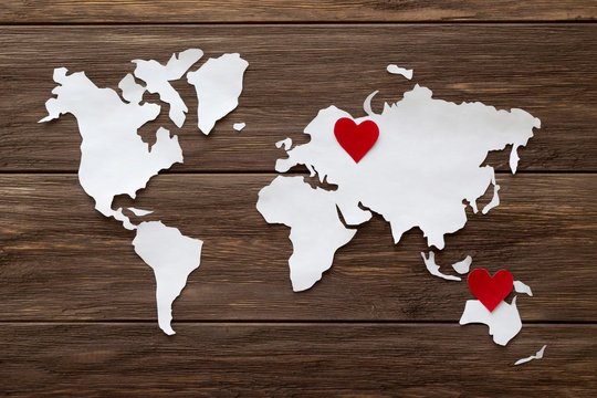 Red felt hearts and world map cutted from white paper on the wooden background. Long-distance relationships concept - Russia and Australia. Flat lay, top view, copy space, mock up