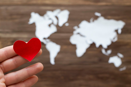 Hand holding red heart and world map cutted from white paper on the wooden background. Love concept. Close-up, soft focus, copy space, mock up
