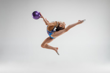 The teen female little girl doing gymnastics exercises with ball on a gray studio background. The...