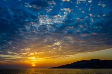 Long shot of dramatic sunrise with intensive cloud cover