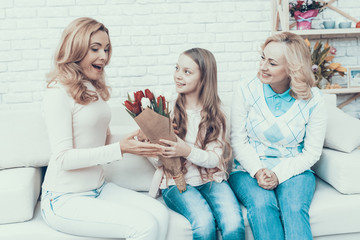 Girl Presents Bouquet of Tulips to Smiling Mother.