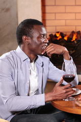 Young African American in a restaurant with a glass of red wine. The concept of rest and communication. Photo in interior.