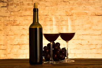 Two glasses of red wine with grapes on table