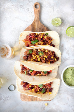 Mexican tacos with meat, beans, tomatoes, corn, paprika and cilantro on wooden board on shabby background.