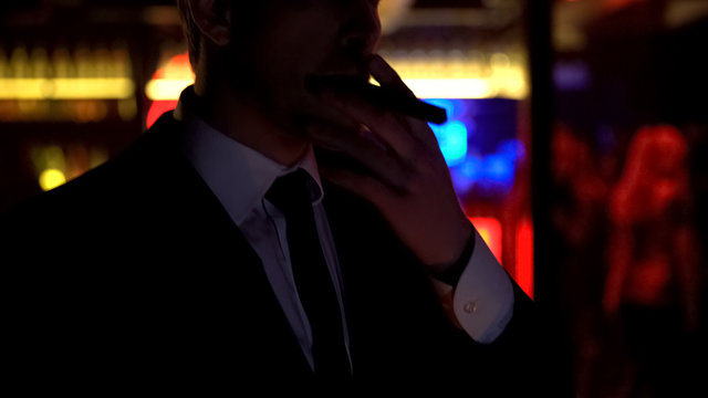 Successful businessman smoking cigar, enjoying evening in elite strip club