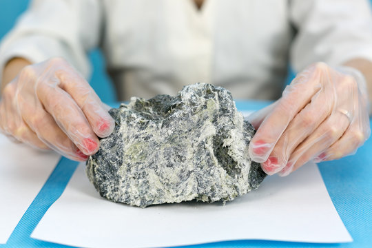 Female hands hold the dangerous mineral asbestos. A girl lab technician is holding asbestos stones for analysis.