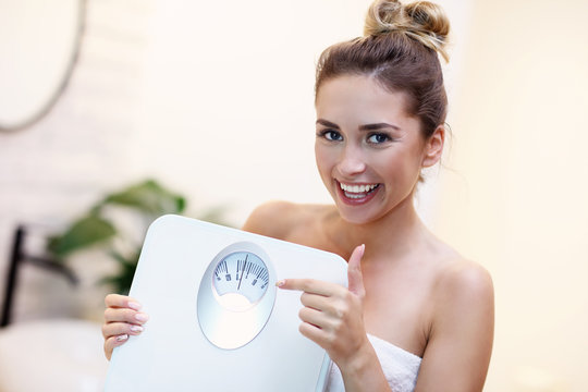 Happy woman holding bathroom scales in bathroom