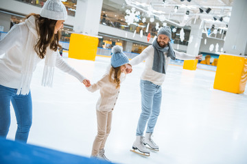happy family in hats and sweaters holding hands while skating together on ice rink