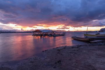 landscape, Floating house whit old wooden boat on shore and sunset at Vajiralongkorn Dam in Kanchanaburi, Thailand.