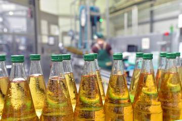 apple juice in glass bottles in a factory for the food industry - bottling and transport // Apfelsaftflaschen in einer modernen Mosterei - Fliessband in der Produktion und Abfüllung