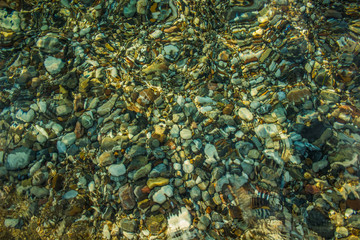 abstract unfocused fuzzy colorful stones on sea bottom surface background through the water
