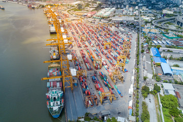 Logistics and transportation of container cargo freight ship with container crane in shipyard. Logistic import export business and transport industry. Aerial view taken from drone.