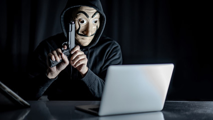Male hoodie hacker wearing mystery mask holding gun while sitting with laptop computer on the table. Ransomware cyber attack or internet security concepts. Anonymous thief committing the crime.