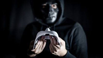 Mystery hoody man wearing broken black mask holding white mask. Anonymous social masking. Major depressive disorder or bipolar disorder. Halloween concept