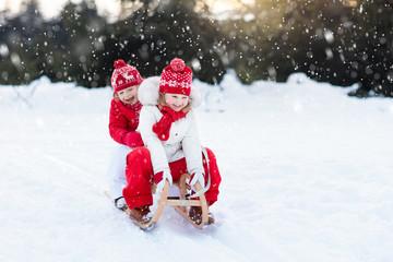 Kids on sleigh. Children sled. Winter snow fun.