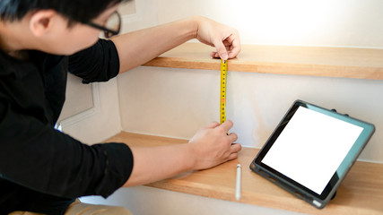 Young Asian worker using tape measure for measuring riser and thread on stair in the house. Writing note and sketching on digital tablet for design information. Housing construction and renovation