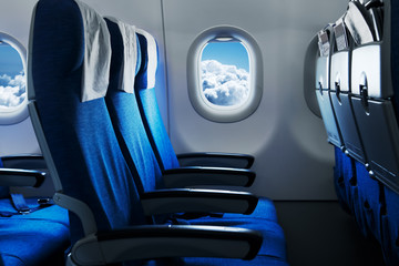 Poster Avion à Moteur Empty air plane seats. Blue sky and clouds in the window. Airplane interior