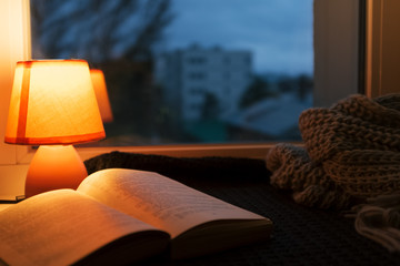 Wool scarf, small table lamp and old vintage book on window sill. Cozy home in the dusk