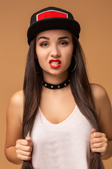 Close up positive portrait of pretty girl with amazing long brunette hair, bright sportive hat, bright make up, crazy funny face.
