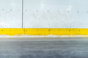 Hockey rink boards with scratched and damaged surface and ice floor