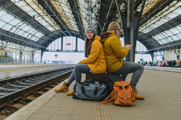 bored couple sit on their bags waiting for train. check phones while waiting