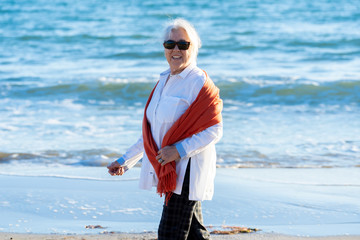 Smiling attractive senior woman walking and enjoying a day at the beach outdoors at sunset.