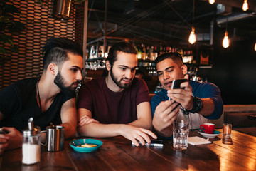 Group of mixed race young men talking and using phone in lounge bar. Multiracial friends having fun in cafe