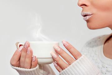Wall Mural - Зимний вязанный дизайн ногтей и макияж губ.Модный маникюр в пастельных оттенках.Горячий напиток.