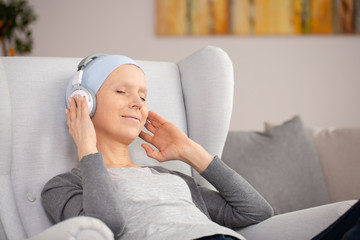 Peaceful woman with headphones and blue headscarf resting at home after cancer treatment