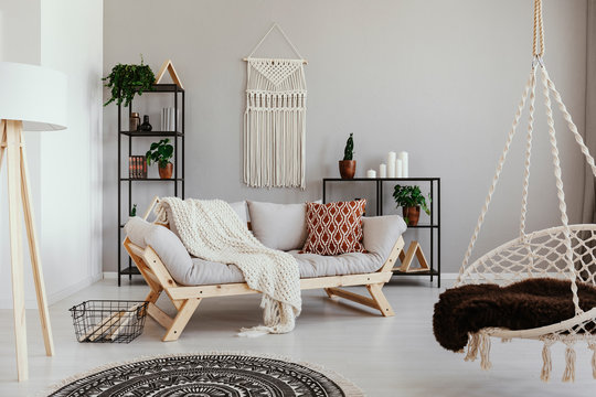 Handmade macrame on the empty wall of bright beige living room with comfortable couch with pillows and white blanket , real photo
