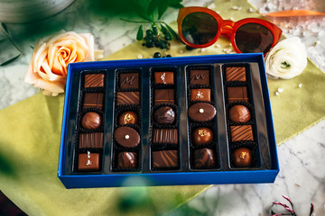 A box of chocolates with sunglasses and roses