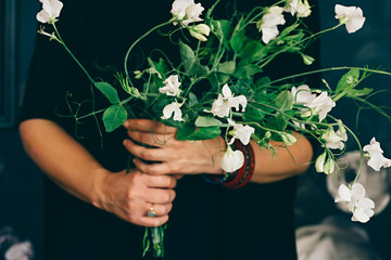 Woman holding bunch of white flowers
